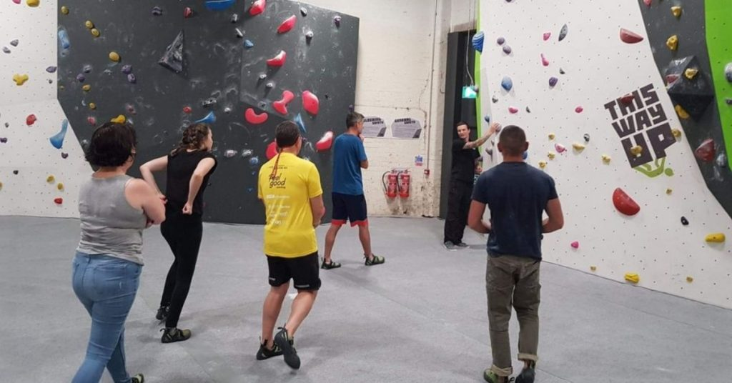 The group approaching the climbing wall, led by Tiff.