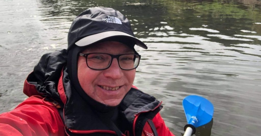 Selfie on Chris, in wet-weather gear, on the water, holding a paddle.