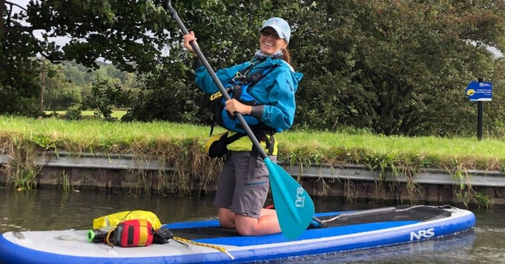 An image of a very happy Lynne, kneeling on her stand-up paddleboard, on the water.